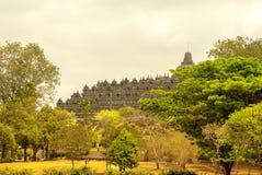 Borobudur a distancia enmarcado por los árboles Fotos de archivo libres de regalías