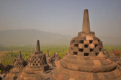 Borobudur Giant Stupas during late sunrise with misty feeling among the forest in the background Stock Photo