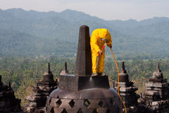 Borobudur Rescue High Pressure Cleaning. Worker cleans the Borobudur Temple in Central Java with a high pressure hose after it was covered in ash by the volcanic royalty free stock image