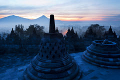 Borobudur temple with Buddha statue, bell stupas and volcano in background Stock Photos