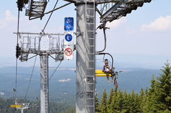Borovets Resort, Bulgaria - July 31, 2016: Mountain biker with his bike on a chairlift heading to Rila mountain hills Royalty Free Stock Image