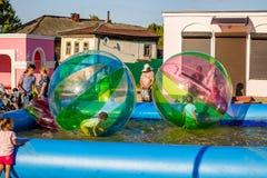 Borovsk, Rusia - 18 de agosto de 2018: Los niños patinan dentro de la bola en el agua imagen de archivo