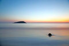 borrão de movimento do mar sob o céu crepuscular vívido do por do sol foto de stock royalty free