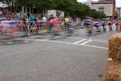 Borrão de movimento dos ciclistas que apressam-se com a volta na raça amadora Foto de Stock