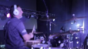 borrão Opinião lateral um baterista profissional que executa na fase iluminação do concerto Projetores no fundo vídeos de arquivo