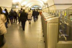 borrão Uma multidão de passagens dos povos com pressa através dos torniquetes eletrônicos na estação de metro em St Petersburg, R foto de stock