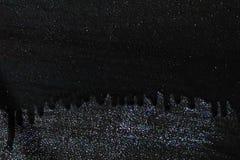 Borrões pretos secados bonitos da pintura na superfície unpainted metálica do fundo, espaço para o texto, pintura artística imagem de stock royalty free