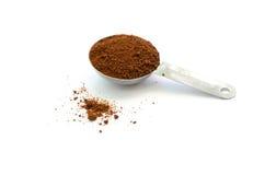 Borra de café na colher inoxidável da tabela no fundo branco Imagem de Stock Royalty Free