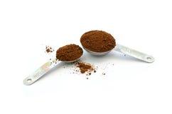 Borra de café na tabela e na colher inoxidáveis do chá no fundo branco Fotografia de Stock Royalty Free
