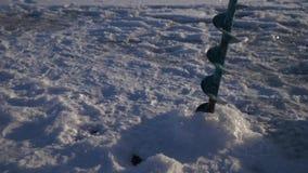 borra hålet i issjön för vinterfiske close upp 4K stock video