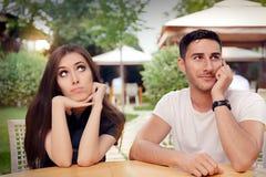 Borrad flickakänsla, medan hennes pojkvän är på telefonen arkivfoto