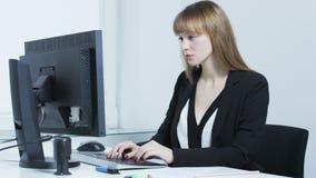 Borrad nätt ung kvinna, medan skriva på ett tangentbord arkivfilmer