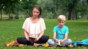 Borrad son medan moderläsebok om barnutbildning, spetsar för föräldrar arkivfoton