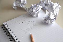 Borre la idea de las palabras con el documento arrugado sobre el escritorio imagenes de archivo