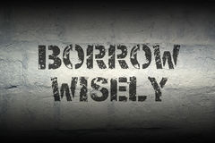 Borrow wisely gr. Borrow wisely stencil print on the grunge white brick wall; specially designed font is used stock images