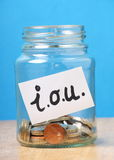 Borrowing Money Concept. A jam jar part filled with british coins for savings has been slapped with a white sticker that says I.O.U. the abbreviation for I Owe Stock Photos