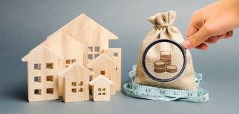 Borsa con la misura di nastro e dei soldi con case di legno Il concetto di un bilancio limitato del bene immobile Sovvenzioni bas fotografia stock libera da diritti