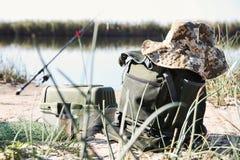 Borsa con la pesca degli elementi essenziali alla riva del fiume fotografia stock libera da diritti