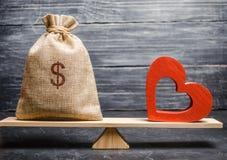 Borsa con soldi e cuore di legno rosso sulle scale Soldi contro il concetto di amore Passione contro il profitto Famiglia o scelt fotografia stock