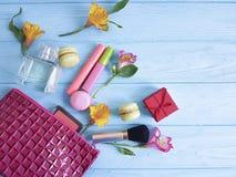 Borsa cosmetica, macaron di legno blu, fiori accessori di volto di fascino, mascara, alstroemeria Fotografia Stock