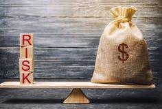 Borsa dei soldi e blocchi di legno con il rischio di parola Il concetto del rischio finanziario Rischi giustificati Investendo in immagine stock libera da diritti