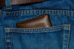 Borsa del cuoio di Brown nella tasca Il portafoglio a metà strada fuori dall'jeans appoggia Blue jeans della tasca con marrone de Fotografie Stock