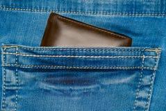 Borsa del cuoio di Brown nella tasca Il portafoglio a metà strada fuori dall'jeans appoggia Blue jeans della tasca con marrone de Immagini Stock