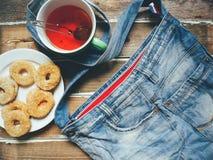 borsa del denim, una tazza di tè e biscotti casalinghi sui bordi di legno Fotografie Stock Libere da Diritti