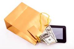 Borsa del regalo dell'oro con una compressa ed i dollari Fotografia Stock Libera da Diritti