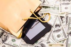 Borsa del regalo dell'oro con una compressa ed i dollari Immagine Stock