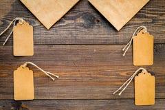 Borsa della carta kraft di Brown per la compera vicino ai prezzi da pagare sullo spazio di legno della copia del modello di vista Immagini Stock