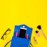 Borsa della donna, prodotti di bellezza, smartphone, vetri su un fondo giallo luminoso, vista superiore Fotografie Stock Libere da Diritti