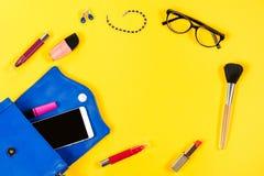 Borsa della donna, prodotti di bellezza, smartphone, vetri su un fondo giallo luminoso, vista superiore Fotografia Stock