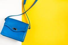 Borsa della donna su fondo variopinto Colori pastelli blu e gialli, vista superiore Fotografia Stock