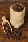 Borsa della iuta in pieno dei chicchi di caffè Fotografie Stock