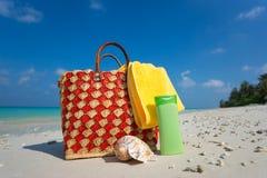 Borsa della spiaggia di estate con le coperture, asciugamano sulla spiaggia sabbiosa Immagini Stock Libere da Diritti