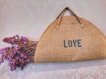 Borsa di amore, fiore porpora secco nella borsa marrone del tessuto fotografia stock