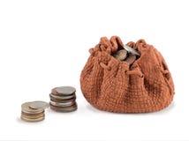 Borsa di argilla con moneу e colonna delle monete isolate su un fondo bianco Concetto di crescita o di investimento Fotografia Stock