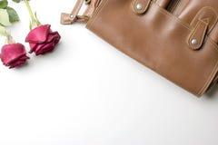Borsa di cuoio di Brown con le rose su fondo bianco Disposizione piana Fotografie Stock