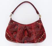 Borsa di cuoio rossa fatta della pelle del pitone su un fondo bianco Gli accessori delle donne di modo La vista dalla parte super immagini stock