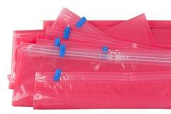 Borsa di plastica rosa della serratura dello zip con il sigillamento blu per imballare i panni del deposito fotografia stock