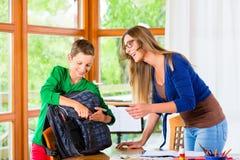 Borsa di scuola dell'imballaggio del figlio e della madre Fotografia Stock
