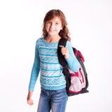 Borsa di scuola sorridente della tenuta della ragazza del bambino su bianco Fotografie Stock Libere da Diritti