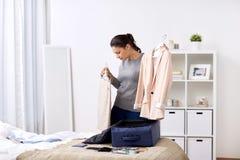 Borsa di viaggio dell'imballaggio della donna a casa o camera di albergo Immagine Stock