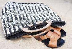 Borsa di vimini della paglia di estate d'annata e sandali di cuoio sulla spiaggia di Catania, Sicilia, Italia fotografie stock