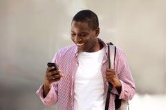 Borsa diritta dello studente di college africano ed esaminare telefono cellulare Fotografia Stock Libera da Diritti