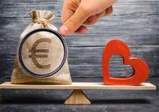 Borsa euro dei soldi e cuore di legno rosso sulle scale Soldi contro il concetto di amore Passione contro il profitto Famiglia o  immagine stock
