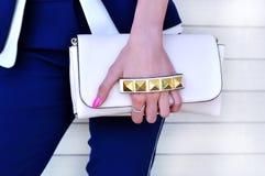 Borsa femminile elegante di stile alla moda e di lusso Ragazza d'avanguardia in vestito blu che tiene piccola borsa di cuoio bian Fotografie Stock