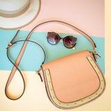 Borsa femminile, sunglass, cappello su un fondo del pastello di colore Immagini Stock