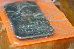Borsa impermeabile arancio del telefono sul bordo di legno Immagine Stock